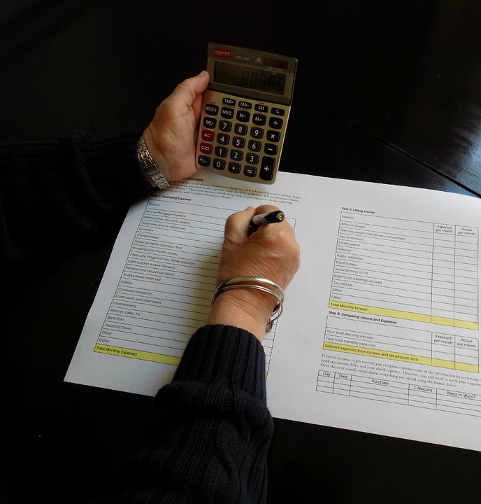 Person holding a calculator while writing on a piece of paper