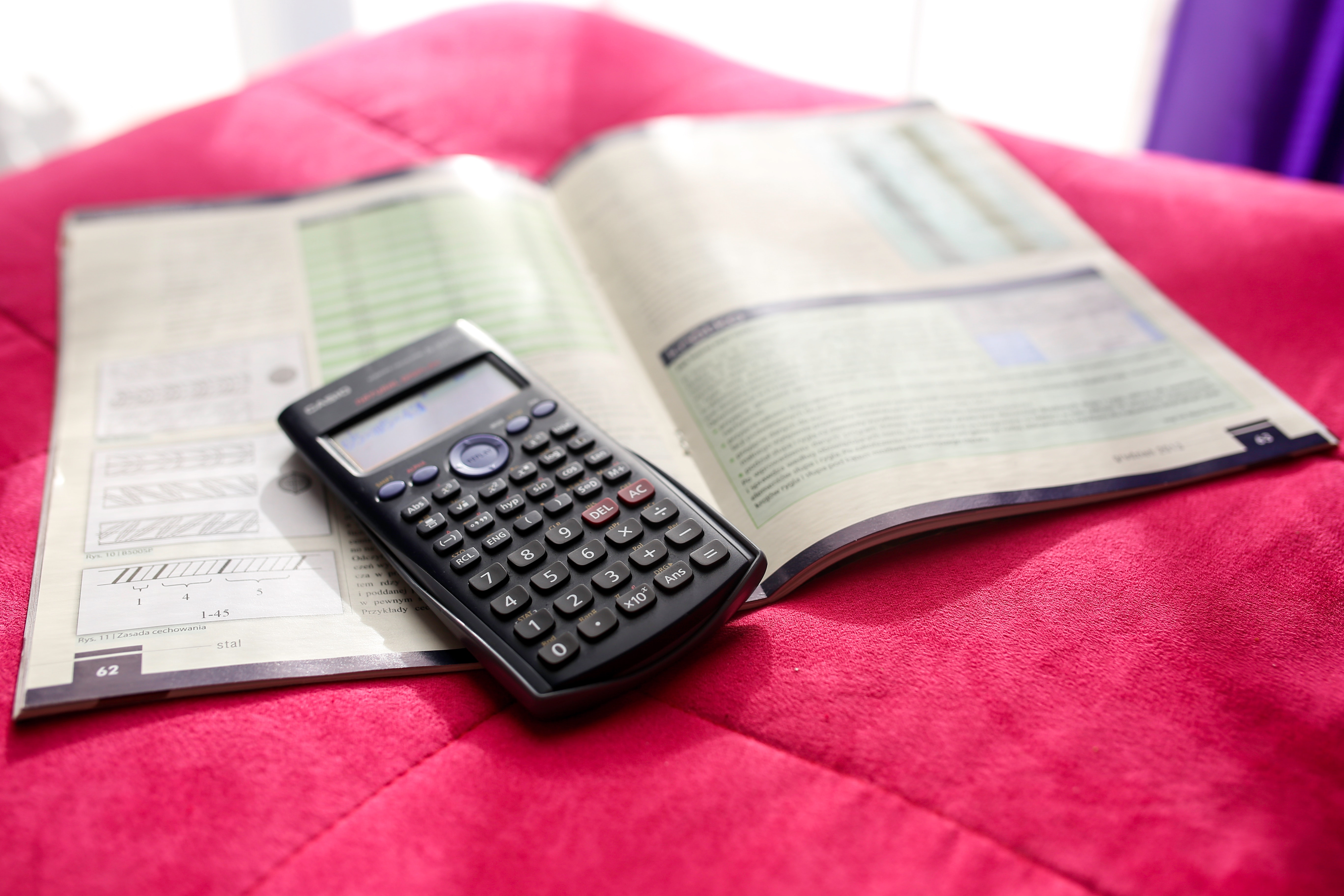 Calculator and a book on top of red fabric